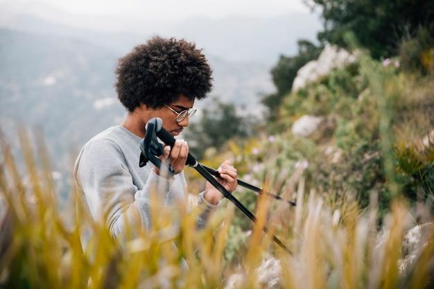 Afrykański młody męski wycieczkowicz trzyma wycieczkować słupa w ręce
