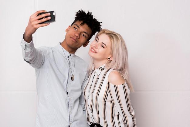 Afrykański nastoletni chłopak bierze selfie z jej dziewczyną na telefonie komórkowym