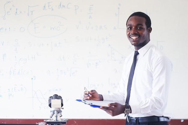 Afrykański nauczyciel uczy i uśmiecha się w klasie łodygi z mikroskopem.