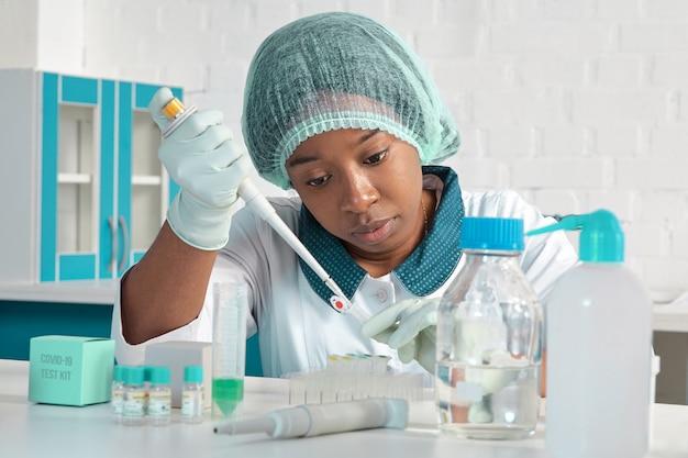 Afrykański naukowiec, asystent techniczny lub technik medyczny w białym płaszczu, kapeluszu ochronnym i rękawiczkach optymalizuje testy pcr na obecność wirusa sars-cov-2 w nowoczesnym laboratorium testowym. wnętrze placówki badawczej.