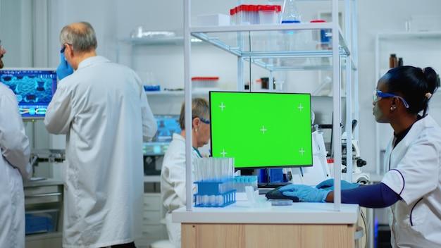 Afrykański naukowiec kobieta pisania na komputerze z zielonym makieta w nowocześnie wyposażonym laboratorium. wieloetniczny zespół mikrobiologów prowadzących badania nad szczepionkami, piszących na urządzeniu z kluczem chromatycznym, izolowany wyświetlacz.