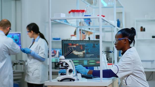 Afrykański naukowiec pracujący w nowocześnie wyposażonym laboratorium z probówkami. wieloetniczny zespół badający ewolucję wirusa przy użyciu zaawansowanych technologii do badań naukowych nad opracowaniem leczenia przeciw covid19