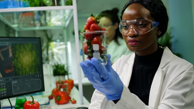 Afrykański naukowiec trzymający szklankę z truskawką wstrzykniętą pestycydami