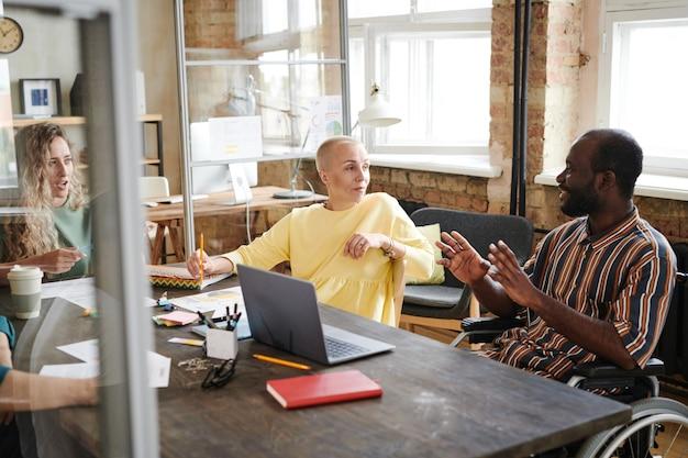 Afrykański niepełnosprawny biznesmen omawiający ze swoimi partnerami nową strategię podczas spotkania biznesowego