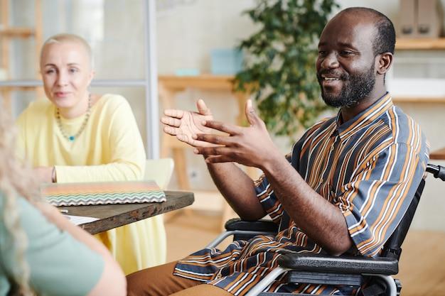 Afrykański niepełnosprawny biznesmen rozmawia z kolegami podczas spotkania biznesowego w biurze