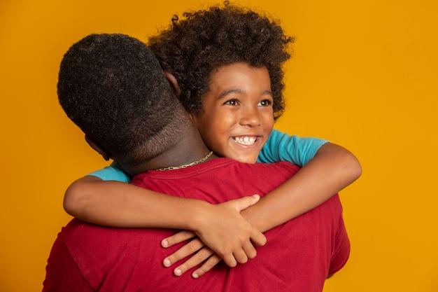 Afrykański ojciec i syn grający w superhero w czasie dnia. ludzie zabawy żółtą ścianę. pojęcie przyjaznej rodziny.