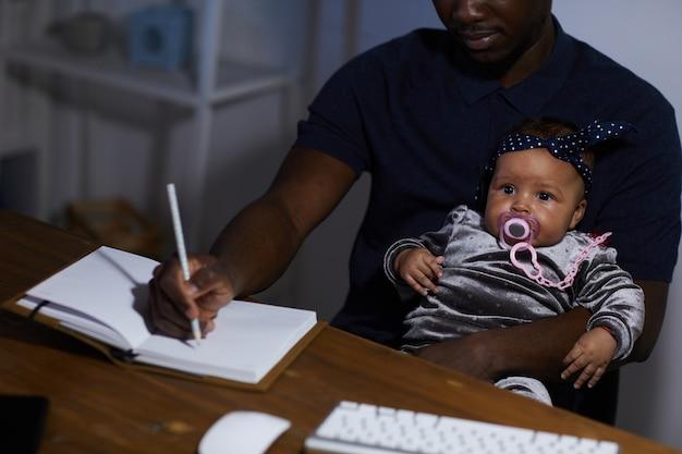 Afrykański ojciec robiąc notatki w notesie, siedząc przy stole z dzieckiem na kolanach
