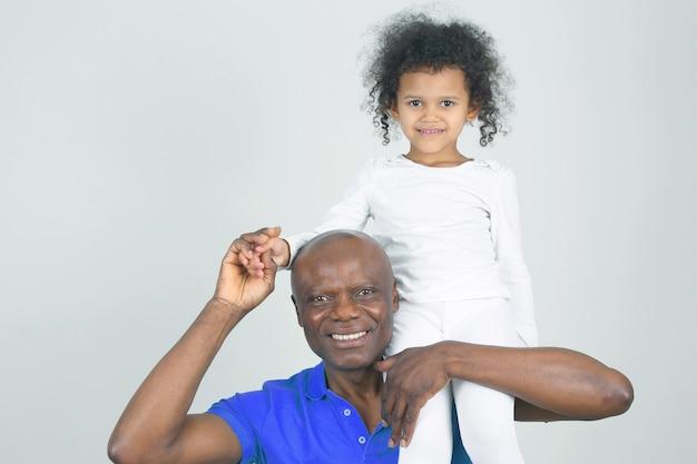 Afrykański ojciec trzymający się na ramieniu córki. miłość i troska w rodzinie między ojcem a córką