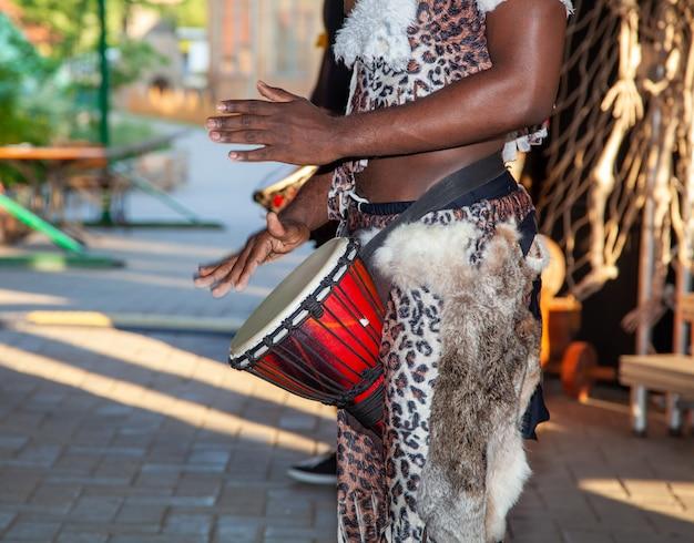 Afrykański perkusista gra na djembe. tradycyjny instrument muzyczny.