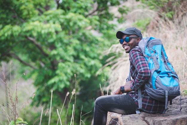 Afrykański podróżnik mężczyzna siedzi na szczycie góry z plecakiem