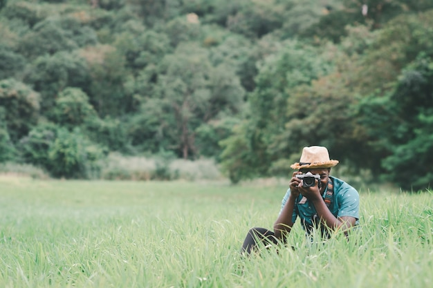 Afrykański podróżnik robi zdjęcie wśród zielonych łąk
