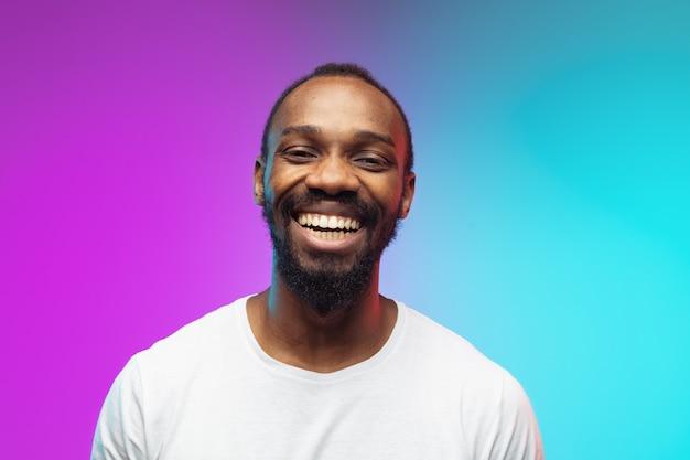 Afrykański portret młodego mężczyzny na gradientowym tle studio w neonowym zbliżeniu