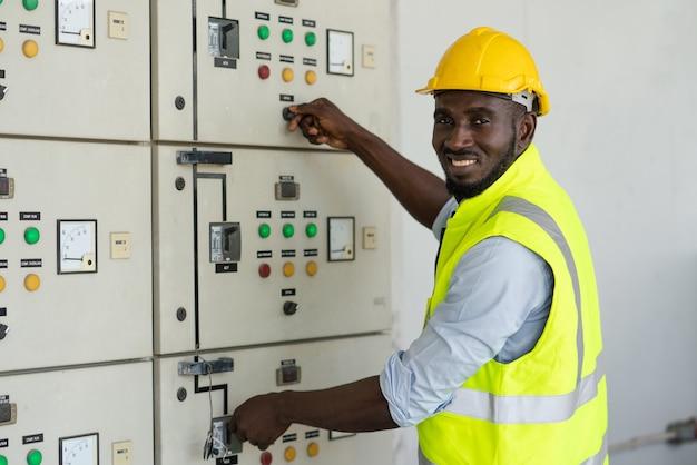 Afrykański pracownik elektryczny otwarty wyłącznik zasilania wyłącznik napięcia w fabryce magazynu