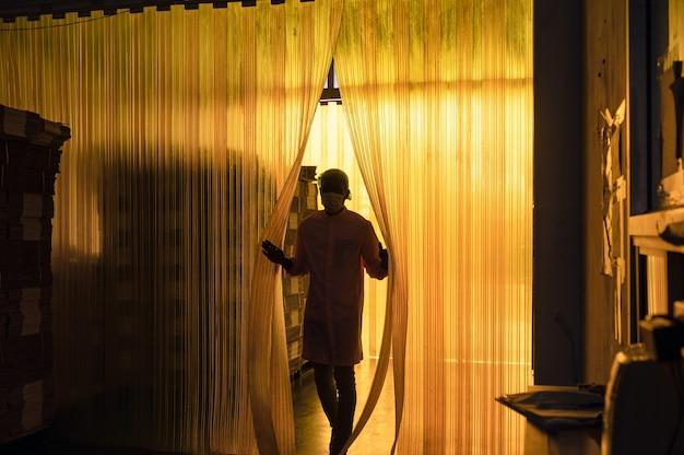 Afrykański pracownik płci męskiej otwierający plastikową zasłonę do magazynu opakowań kartonowych w zakładzie przetwórstwa napojów