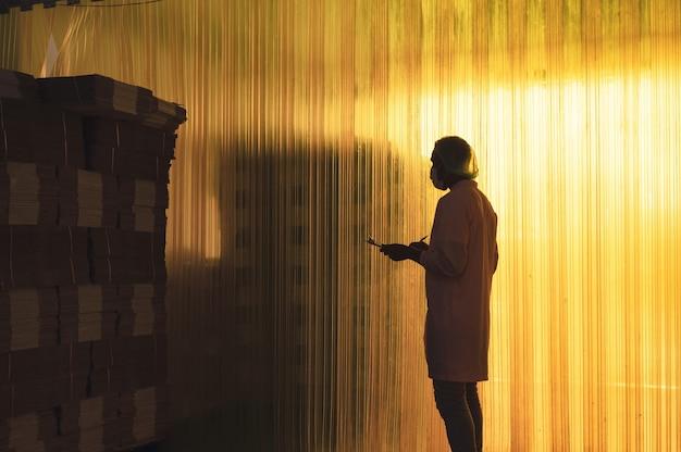 Afrykański pracownik płci męskiej ze schowkiem sprawdzającym zapasy płaskiego kartonu ułożonego w magazynie w przetwórni napojów