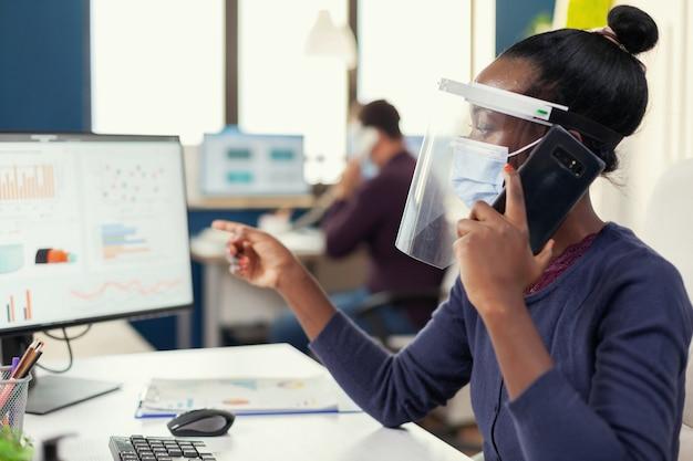 Afrykański pracownik rozmawia na smartfonie w biurze nosząc maskę przeciwko koronawirusowi