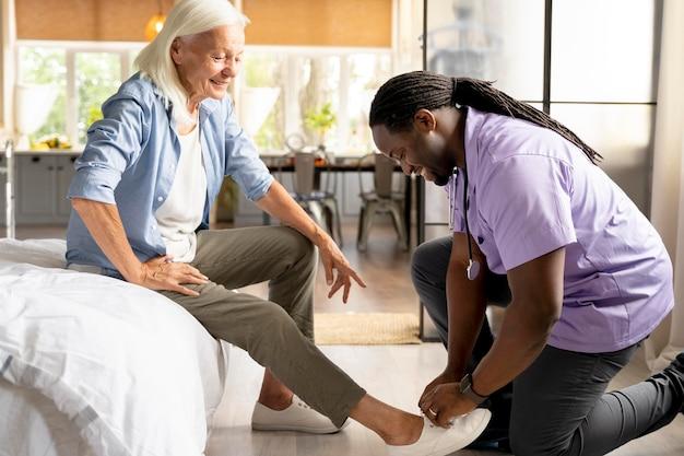Afrykański pracownik socjalny opiekujący się starszą kobietą