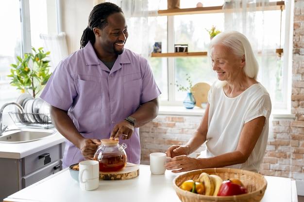 Afrykański pracownik socjalny pomaga starszej kobiecie