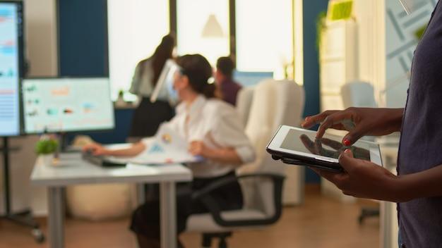 Afrykański pracownik za pomocą tabletu stojącego w pokoju biurowym i zespół analityków finansowych pracujących w tle. wieloetniczni współpracownicy szanujący dystans społeczny w firmie podczas globalnej pandemii