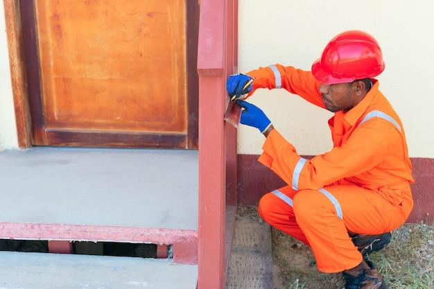 Afrykański robotnik w kombinezonie. afrykański mężczyzna dokonujący pomiaru poza domem