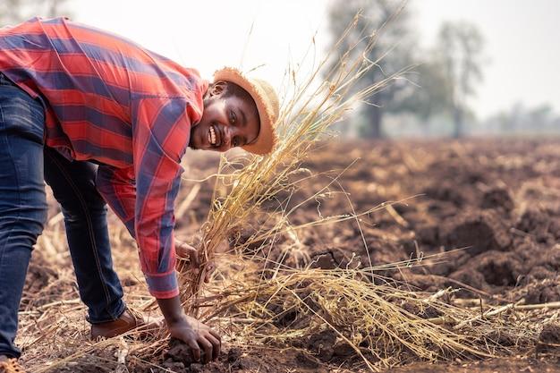 Afrykański rolnik sprawdzający i przygotowujący glebę do sadzenia. koncepcja rolnictwa lub uprawy