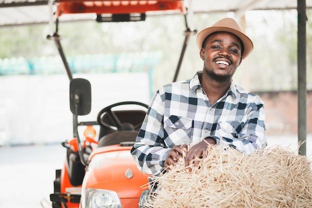 Afrykański rolnik stojący z belami słomy ryżu i traktorem. koncepcja rolnictwa lub uprawy