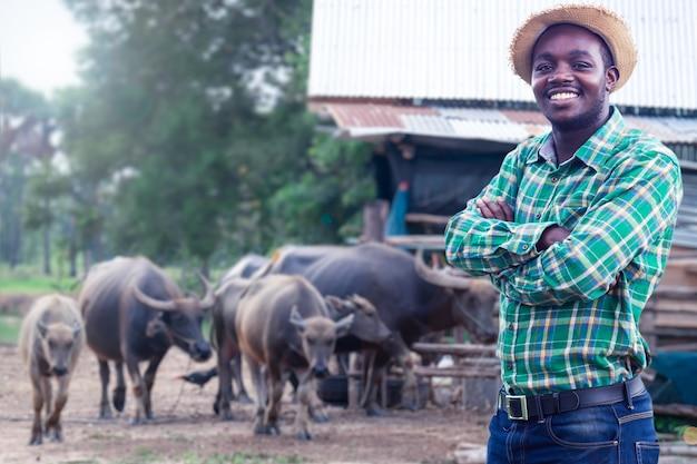 Afrykański rolnik z kapeluszem stoi na farmie bawołów wodnych. koncepcja rolnictwa lub uprawy