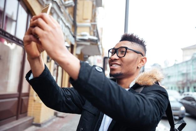 Afrykański szczęśliwy człowiek trzyma swój telefon w ręce i zrobić selfie na zewnątrz.