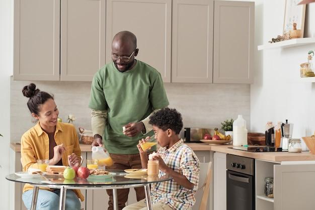 Afrykański szczęśliwy ojciec gotuje śniadanie dla swojej rodziny podczas jedzenia przy stole w kuchni