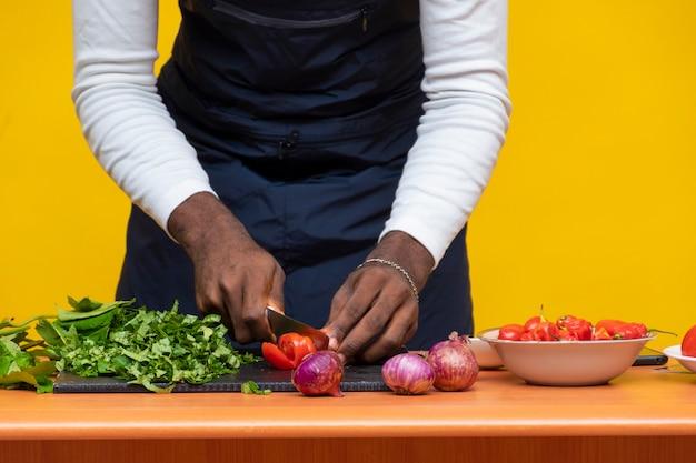 Afrykański szef kuchni sieka pomidora