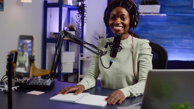 Afrykański twórca macha do kamery, uśmiechając się i rozmawiając z publicznością podczas podcastu za pomocą smartfona