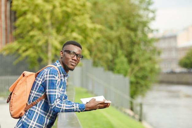 Afrykański uczeń czyta outdoors