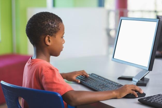 Afrykański uczeń używa komputer w sala lekcyjnej
