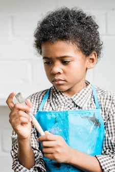 Afrykański uczeń w niebieskim fartuchu patrząc na pędzel w ręku, stojąc przed kamerą w studio