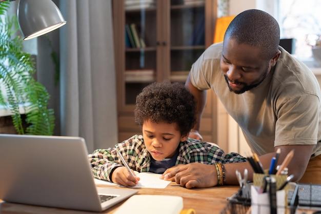 Afrykański uczeń w stroju codziennym robi notatki w zeszycie, podczas gdy jego ojciec pochyla się nad stołem, wskazuje na stronę i coś mu wyjaśnia