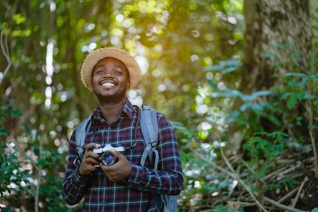 Afrykański wolność mężczyzna podróżnika mienia kamera z plecak pozycją w zielonym naturalnym lesie.