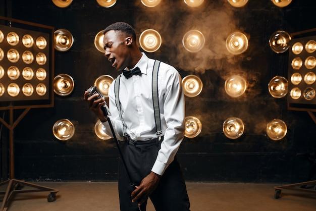 Afrykański wykonawca jazzowy śpiewa na scenie. czarny jazzman występuje na scenie z reflektorami