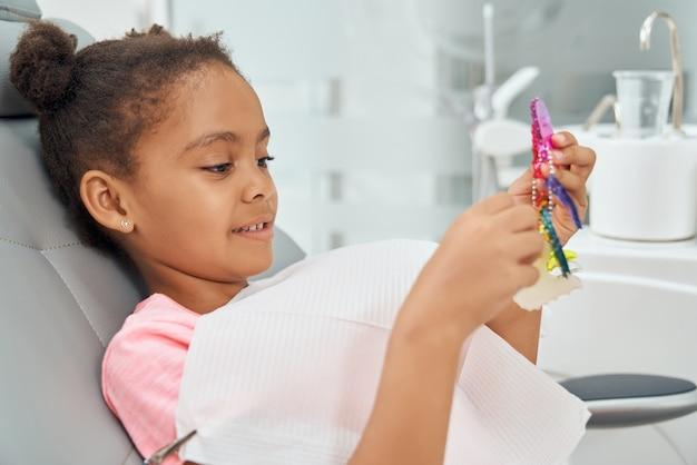 Afrykańskie dziecko siedzi w fotelu i trzymając aparat ortodontyczny.