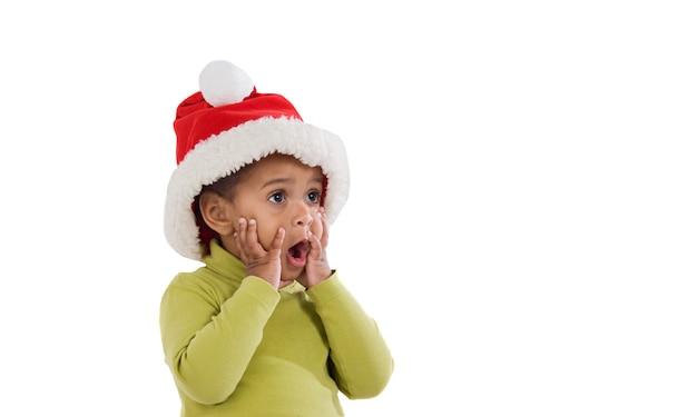 Afrykańskie dziecko w czerwonym świątecznym kapeluszu wygląda na zaskoczonego na białym tle
