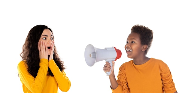 Afrykańskie dziecko z megafonem i zdziwiona dziewczyna nastolatka na białym