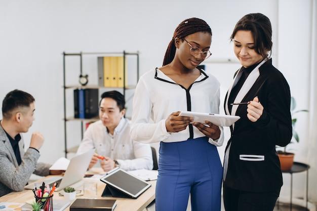 Afrykańskie i kaukaskie białe kobiety za pomocą tabletu z międzyrasową grupą biznesmenów