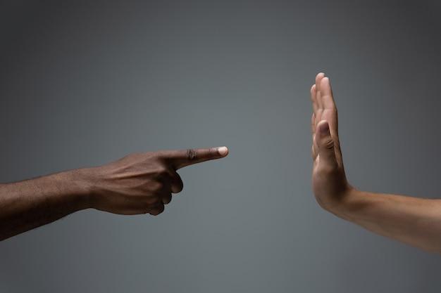 Afrykańskie i kaukaskie dłonie gestykulują na szarym tle studyjnym