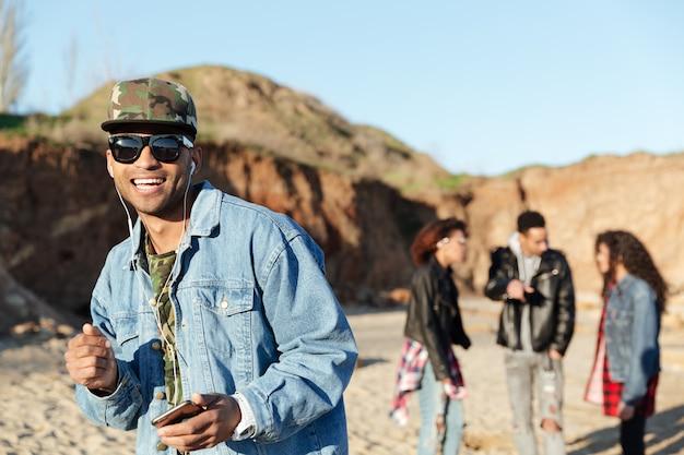 Afrykańskiego szczęśliwego młodego człowieka słuchająca muzyka z słuchawkami