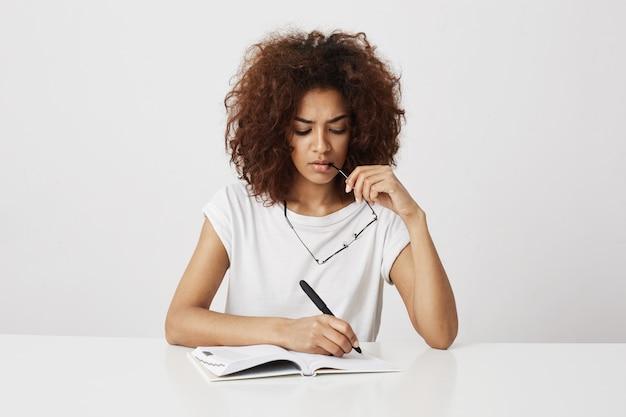 Afrykańskiej dziewczyny myślący writing w notatnika obsiadaniu przy stołem nad biel ścianą. skopiuj miejsce