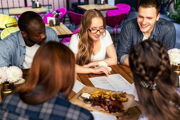 Afterworks nieformalne spotkanie kolegów z pracy w małej kawiarni, dziewcząt i chłopców