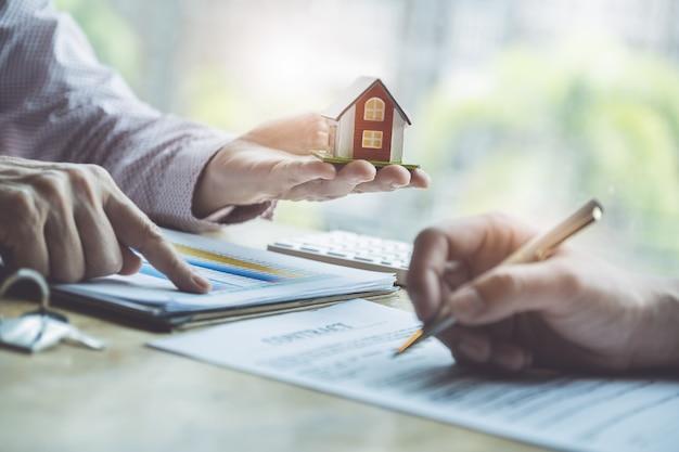 Agenci nieruchomości omawiający pożyczki i stopy procentowe na zakup domów