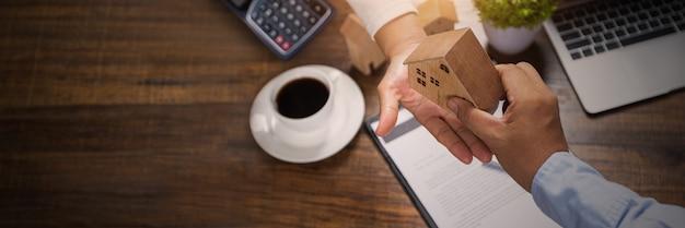 Agencja banku biznesowego trzyma model domu i daje propozycję klientowi, pożyczka mieszkaniowa w tanim interesie na zakup domu, a kondominium kończy kontrakt na koncepcji nieruchomości.