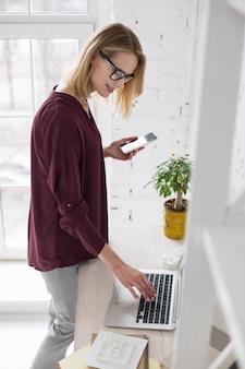 Agenda online. przyjemny szczęśliwy bizneswoman używa laptop i trzyma telefon