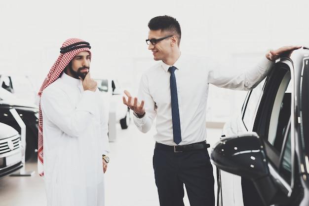 Agent demonstrujący samochód arabski myślący klient.