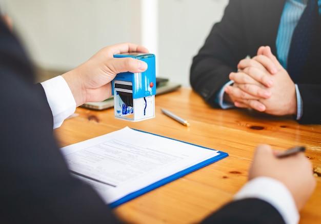Agent ds. sprzedaży nieruchomości w domu przegląda dokumenty, które zostały zatwierdzone dla kredytu kupującego w domu.